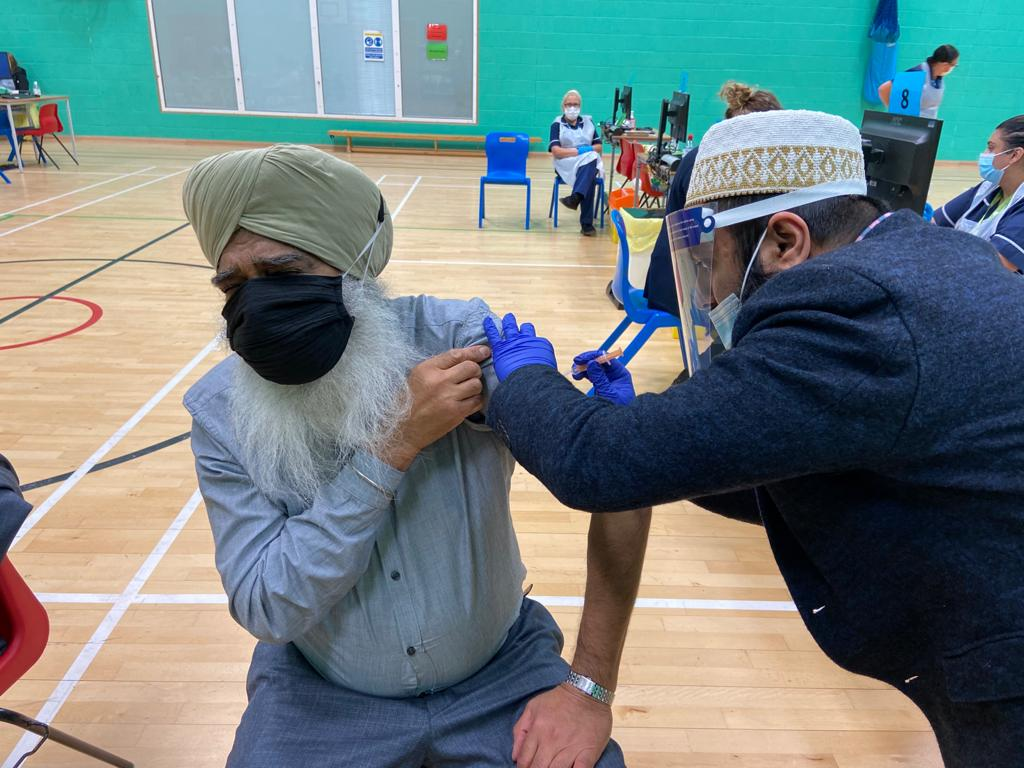 Bohra giving Covid-19 vaccine to elderly man